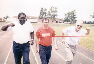 Photograph- Mississauga Track Club:  Three Men running past Finish Line