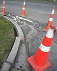 Pylons around damaged pavement and a cracked curb