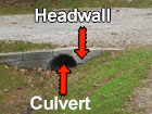 A picture of a ditch with labels identifying the culvert and the headwall.