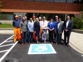 People standing in front of new dynamic symbol of access painted on ground.