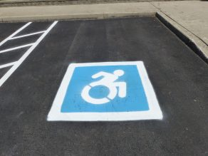 Dynamic symbol of access painted on pavement.