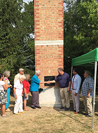 Brick chimney swift tower with people gathered around