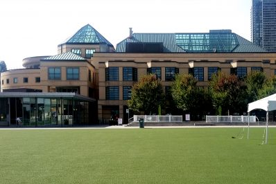 Green space on Celebration Square facing trees and the glass pavilion entrance to the Central Library building