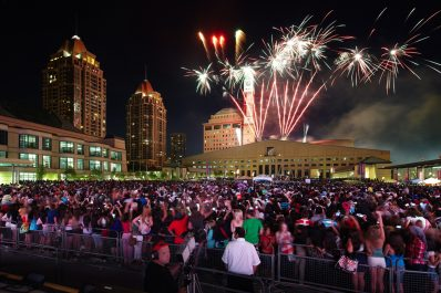 A large crowd of people in the square watching fireworks light up the sky over City Hall building at night