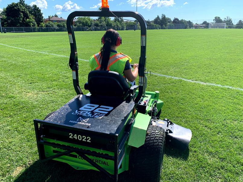 Staff worker operating grass mower
