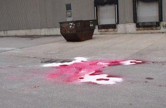 Red powdered dye on ground beside catchbasin
