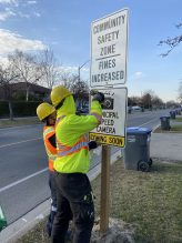 Crews installing signage