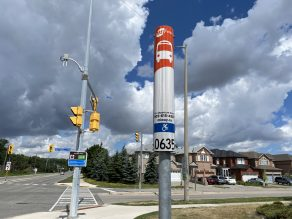 Metal pole with the orange and white MiWay stop sign and bus stop number 0635.