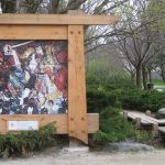 Tile mosaic of photos in a wood frame in a park