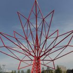 Red metal sculpture of a maple leaf