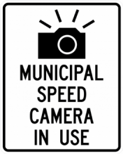 Black and white traffic sign with image of a camera that says municipal speed camera in use