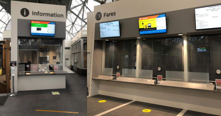 Empty interior of station with new info booth to the left, and fares booth to the right with digital screens above the counter.