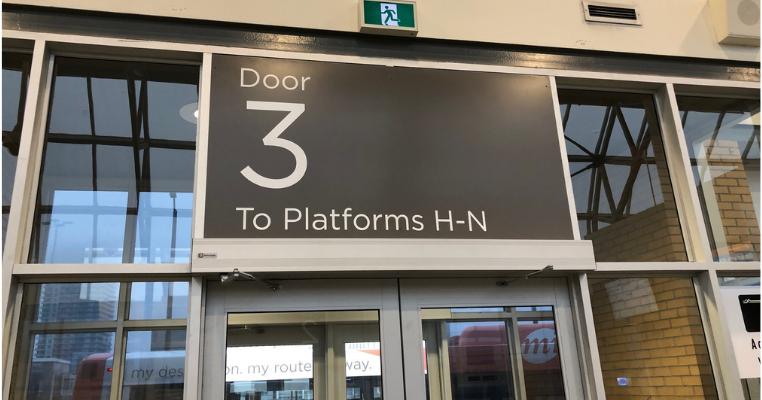 Large sign above door that reads Door 3 To Platforms H-N.