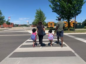 Family walking with two young girls walking across crosswalk towards school