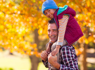 A father and son in an autumnal park setting.