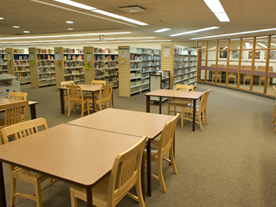 Interior of library showing tables, chairs and bookshelves