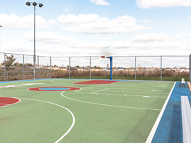 Empty outdoor basketball court with hoop, fencing and lights