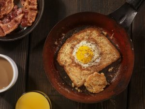 Frying a piece of bread with an egg in the middle in a frying pan. Commonly called egg-in-a-hole