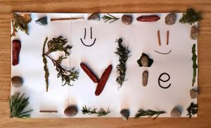 Name Kylie spelled out with nature pieces like sticks, small branches, and rocks