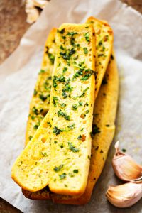 french bread cut in half with butter and herb spread