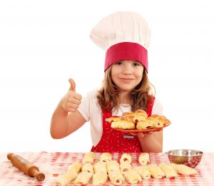 Girl in a chef's hat showing thumbs up in front of a table of stuffed pizza rolls