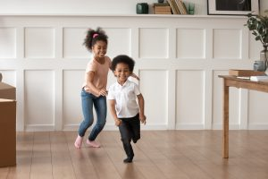 A boy and girl chasing each other inside