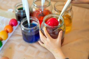 little girl dipping eggs into dye