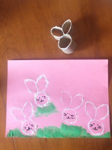 Craft activity using paper roll cut into a bunny shape and used as a stamp on pink paper