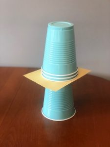 Light blue plastic drink cups stacked on top of each other separated by a cardboard square