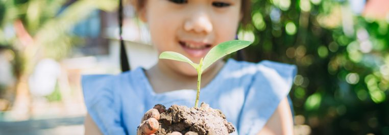 Cute kid planting a tree for help to prevent global warming or climate change and save the earth. Picture for concept of Earth Day to encourage people about the environmental protection.