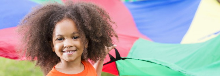 A girl at summer camp holding parachute.