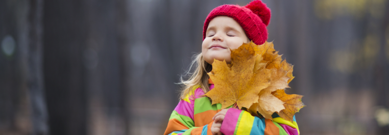 Little girl in a multicoloured coat and red hat hugging fall leaves