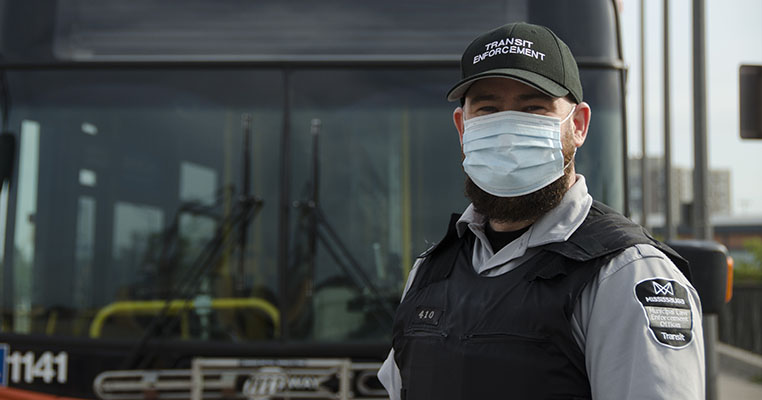 Transit Enforcement Officer in front of bus
