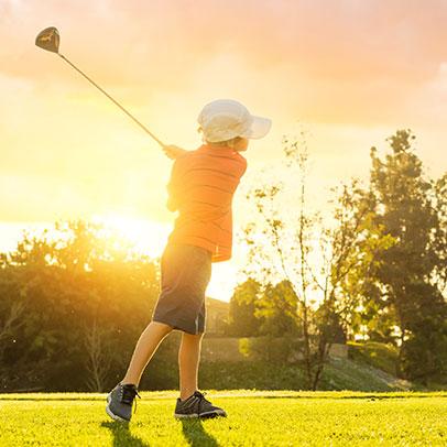 Youth swinging golf club at sunrise