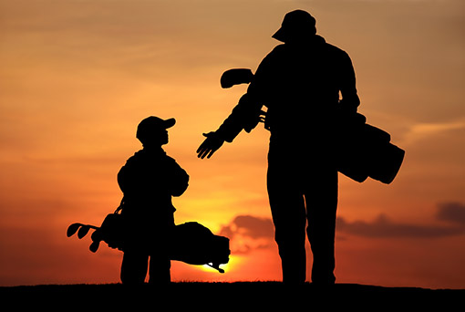 Silhouette of parent and child with golf bags walking into the sunset.