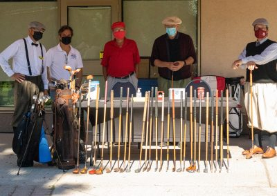 Councillor and Historical society members stand with display of golf artifacts and memorabilia
