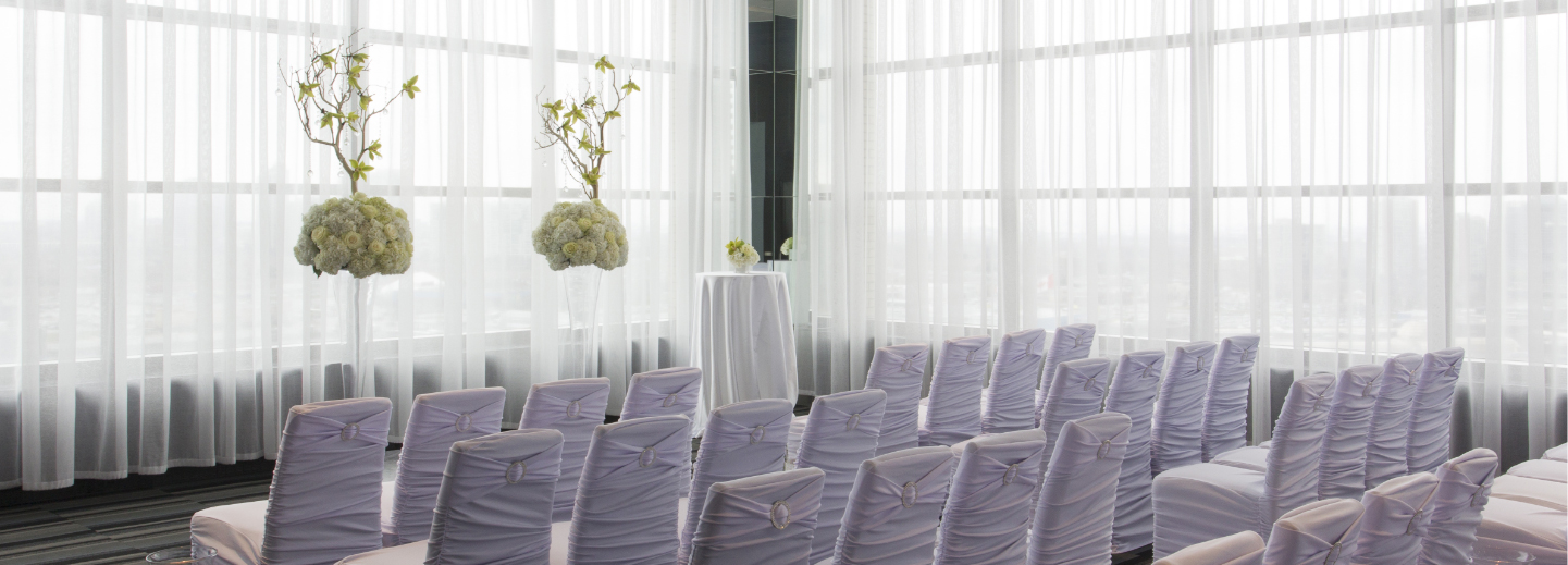 White chair covers in a wedding ceremony setup at C Banquets