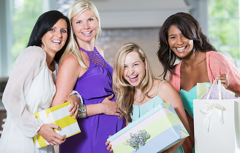 Multiracial group of four women holidng gifts and enjoying a baby shower