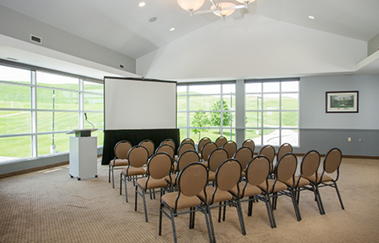 Rows of brown chairs in front of a projector screen and podium overlooking the golf course