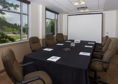 Brown comfortable office chairs and black table linen in a boardroom setup