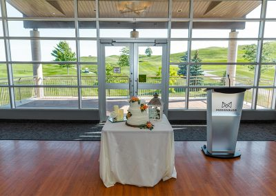 Wedding cake and podium setup on dancefloor with rolling hills in view behind windows