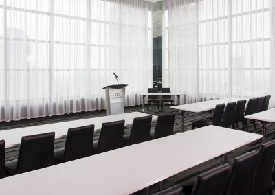 Black chairs and white tables in classroom setup with microphone and podium