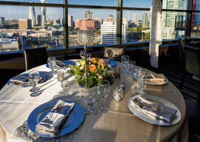 Round table with glassware and place settings and a skyline view