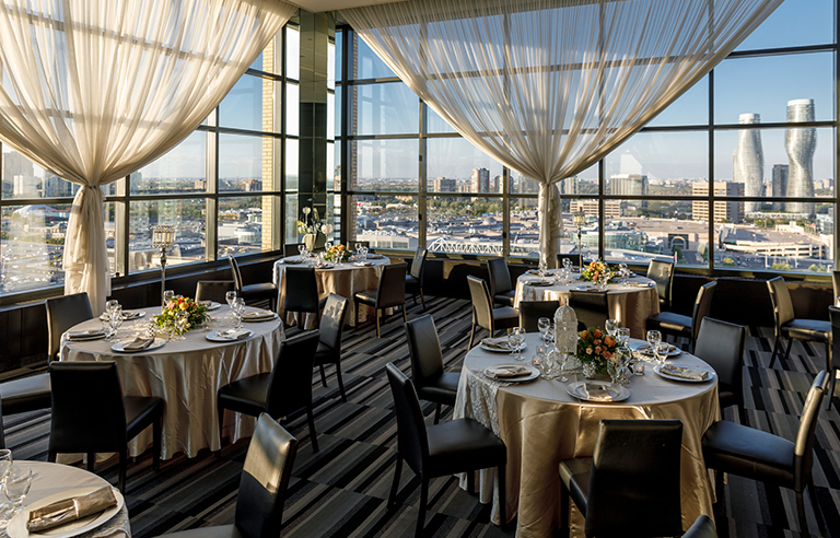 Round tables with gold tablecloth and black chairs overlooking the Mississauga skyline