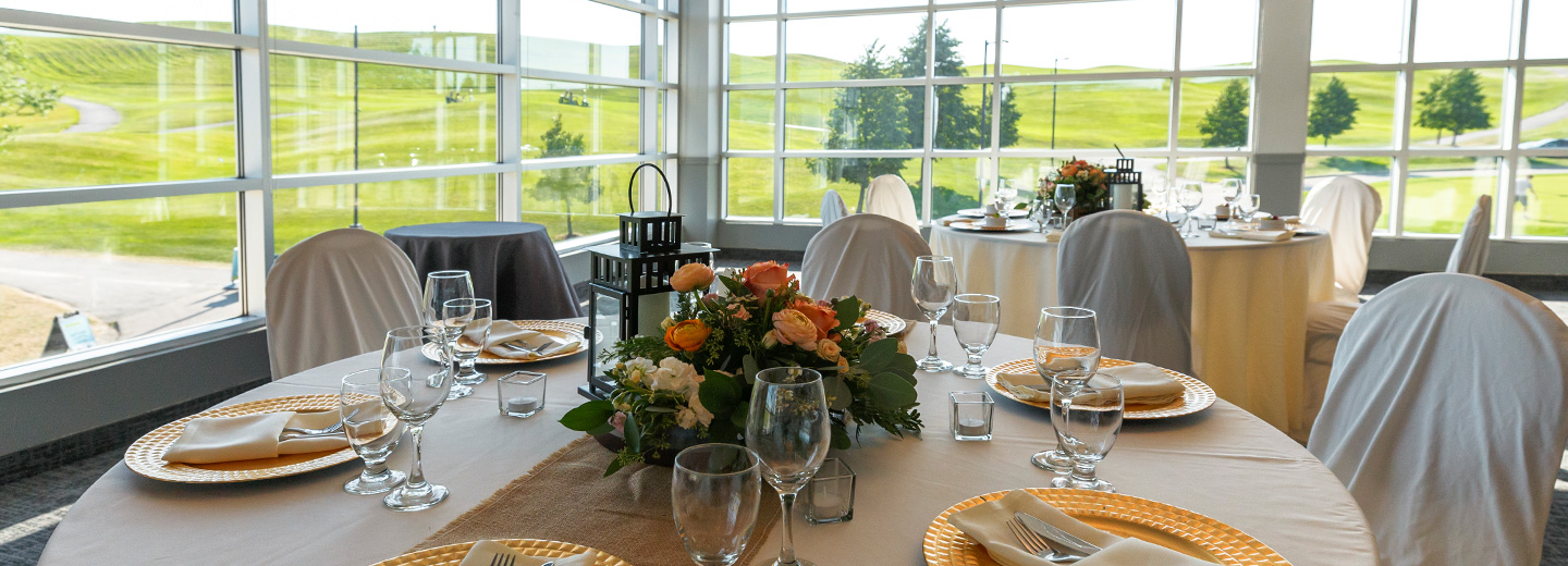Brown and beige tables with natural centrepieces overlooking the fairway at BraeBen Golf Course
