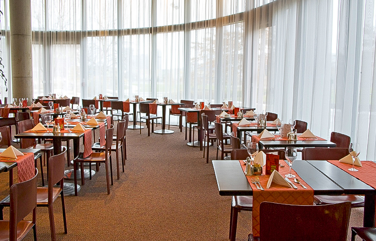 Curtained windows provide natural light in restaurant dining room