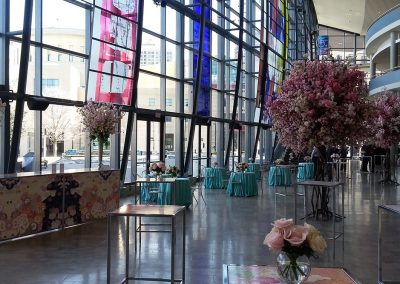Pink leaf trees with teal table covers in LAC atrium